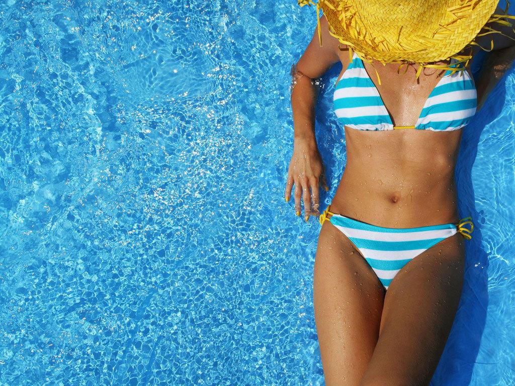 Девушка в полосатом купальнике в воде